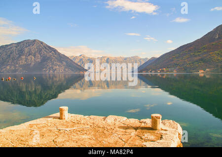 Kotor Bay with dramatic mountain reflections and Perast and Lovcen Mountain in the background - Stock Photo