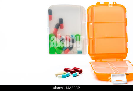 Orange pills box with colorful capsule pills isolated on white background with copy space. Prepare medicine before work or travel abroad concept. - Stock Photo