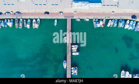 Aerial bird's eye view of Zygi fishing village port, Larnaca, Cyprus. Bird eye view of aligned fish boats moored in the harbour, docked yachts, pier,  - Stock Photo