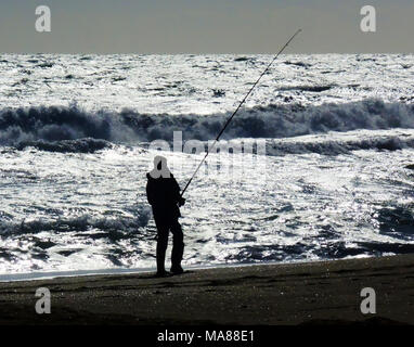 A fisherman silhouetted against the ocean. - Stock Photo