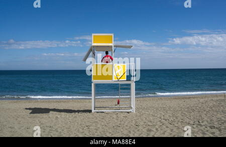A lifeguard looks out to sea from his cabin on a deserted beach. - Stock Photo