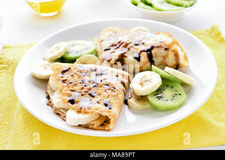 Crepes with banana, kiwi slices and chocolate sauce. Close up view - Stock Photo