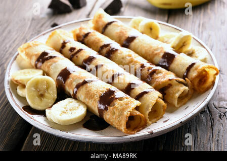 Dessert crepes roll with banana slices on wooden table. Close up view - Stock Photo