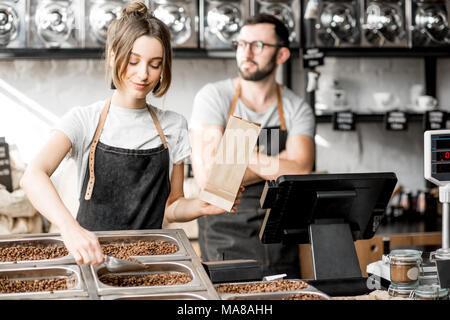 Woman seller filling paper bags with coffee beans while working in the coffee store - Stock Photo