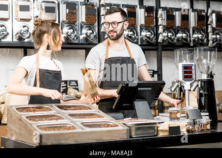 Two sellers in uniform filling bags with coffee beans while working in the coffee store - Stock Photo