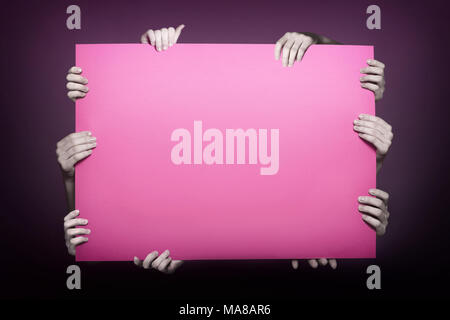 Pink sheet paper. Large banner in the hands of a woman closeup isolate on a black background. Concept copy space - Stock Photo