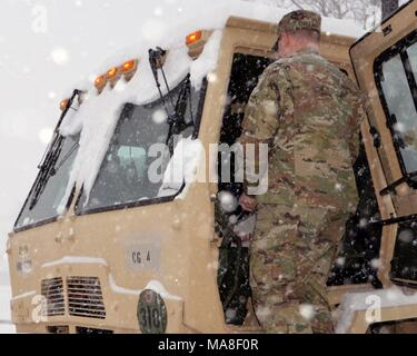 A New York Army National Guard Soldier from the 42nd Combat Aviation Brigade based in Latham, NNew York prepares his vehicle for missions as a massive snow storm hits New York, March 14, 2017. () - Stock Photo