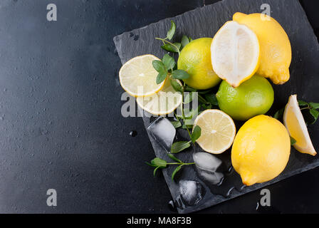 Top view of ice cubes and mojito cocktail ingredients on black slate board, cocktail drinks concept - Stock Photo