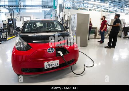 Three National Renewable Energy engineers work on the Electric Vehicle Supply Equipment (EVSE) and PV inverter as part of a 'smart-home-in-the-loop experiment, ' using a red, Toyota Scion, electric car, parked in a laboratory, at the Systems Performance Lab at the Energy Systems Integration Facility (ESIF), image courtesy of the US Department of Energy, July 11, 2016. ()