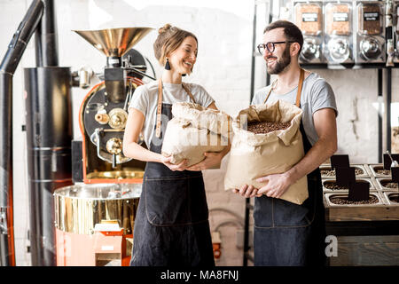 Portrait of a two happy baristas in uniform standing with bags full of coffee beans at the coffee store - Stock Photo