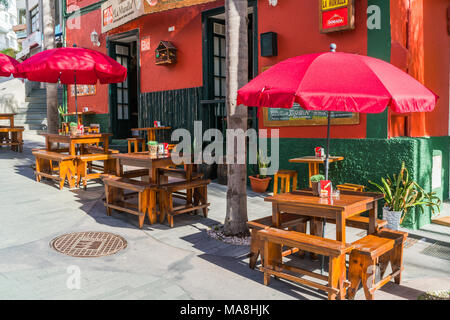PUERTO DE LA CRUZ, TENERIFE - 20 MARCH 2018: Wooden tables on the street outside of a small bar in one of Tenerife's top resorts, Puerto de la Cruz lo - Stock Photo