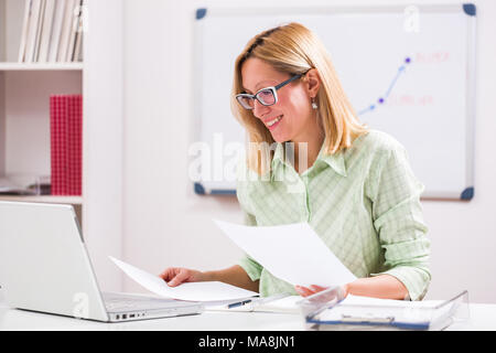 Happy businesswoman is working in her office. - Stock Photo