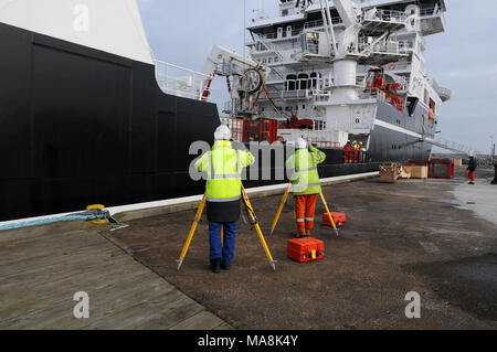 Surveyors carrying out calibration checks on a vessel docked in Blyth Port, Northumberland, England. - Stock Photo