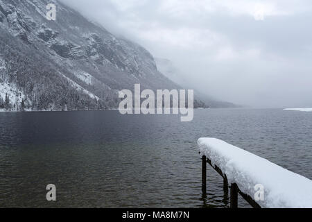 Little pier covered with snow on a lake on a cold winter day - Stock Photo