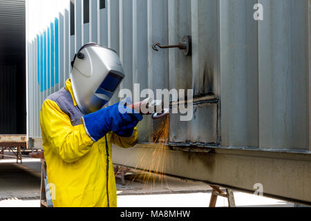 Industry worker with grinding metal to repair container structures manufacture workshop. Worker grinding in factory industry. - Stock Photo