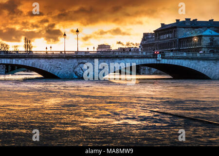 Pont au Change at sunrise with reflection of sky on the swollen Seine surging over submerged road during the Paris flood of January 2018 - Stock Photo
