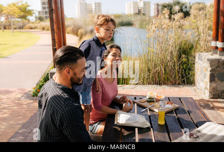 Cheerful couple with their child having a day out. Family sitting in a park with snacks for picnic. - Stock Photo