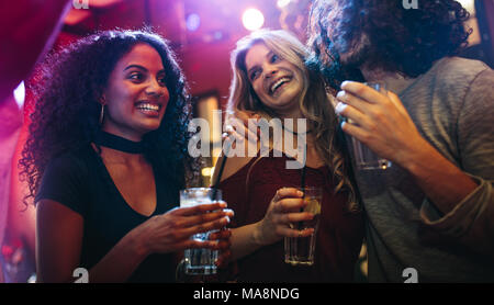 Happy young women partying friends at bar. Group of friends having a good time at nightclub. - Stock Photo