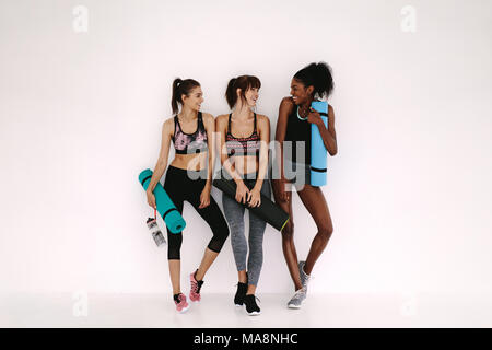 Group of female friends in sportswear smiling together while standing in a gym after yoga workout. Women standing by a wall with exercise mat. - Stock Photo