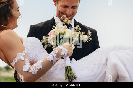 Happy groom carrying beautiful bride with flowers in hand. Newlywed couple with bouquet outdoors on their wedding day. - Stock Photo