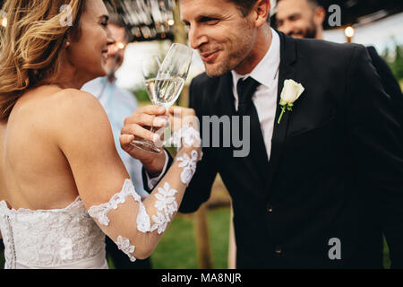 Newlyweds clinking glasses and enjoying romantic moment together at wedding reception outside. Bride and groom drinking champagne at wedding party. - Stock Photo