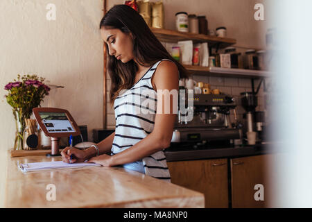 Woman standing at the billing counter of her cafe noting orders. Restaurant owner making notes standing at the billing counter.