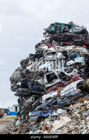 Dumping ground. Scrap metal heap. Compressed crushed cars is returned for recycling. Iron waste ground in the industrial area. Stacked automobile - Stock Photo