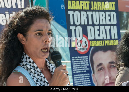 A woman reads a scathing account of the human rights abuses by Israeli forces, aided by Ga4S at the sotp Stop 4S protest outside G4S AGM at Excel London. - Stock Photo