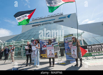 Inminds protesters with 'Boycott Israel' flags give a presentation outside the Excel Centre about human rights abuses by the Israeli government, aided by G4S, at Stop 4S protest outside G4S AGM at Excel London. - Stock Photo