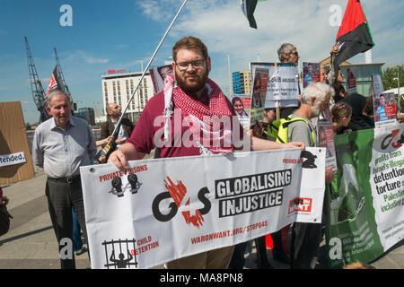 A man holds a War on Want banner 'G4S Globalising Injustice' at the Stop G4S protest outside G4S AGM at Excel London. - Stock Photo