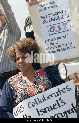 Protesters and placards at the Stop G4S protest outside G4S AGM at Excel London. One of them asks where is the justice for Jimmy Mubenga, killed in an enforced deportation by G4S staff. - Stock Photo