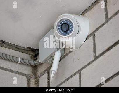 Video surveillance camera on a brick wall - Stock Photo