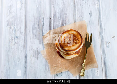 Stack of  homemade pancakes no butter or syrup  on wooden white  table, honey and coffee in the background, subdued morning lighting and breakfast set - Stock Photo