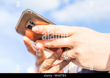 Young woman's hand with diamond engagement ring princess cut, gold outside outdoors blue cloudy sky, closeup of smartphone phone holding - Stock Photo