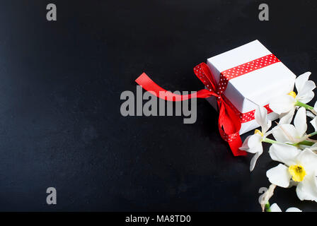 Top view  bouquet of  daffodils and gift box with red ribbon  on the black background.  flowers background concept  Copy space - Stock Photo