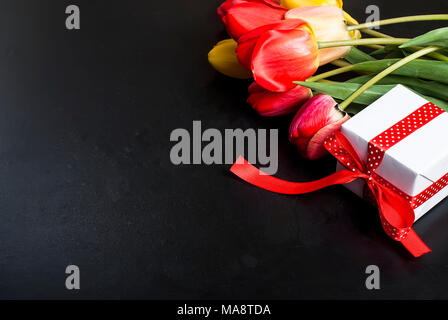 A bouquet of red tulips and gift box with red ribbon on a black background. Copy space. - Stock Photo