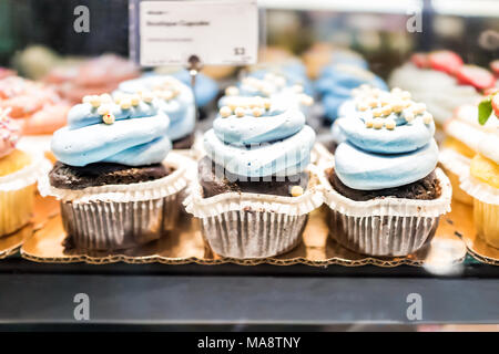 Macro closeup of chocolate cupcakes on display in bakery in muffin paper liners with blue blueberry icing cream - Stock Photo