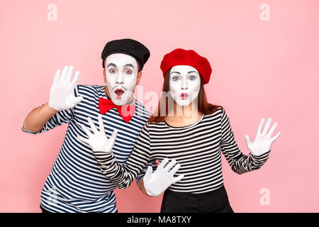 Closeup portrait of handsome couple with shocked face. Clown, artist , pantomime . Studio shot, pink background - Stock Photo