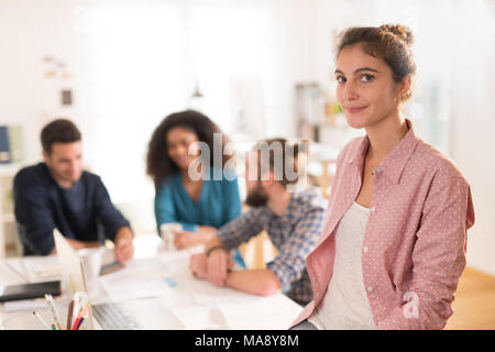 At office. Portrait of a young woman looking at the camera. In t - Stock Photo