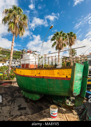 Camara de Lobos, Madeira, Portugal - December 10, 2016: A colorful wooden fishing boat on the shore of fishing village Camara de Lobos near Funchal, M
