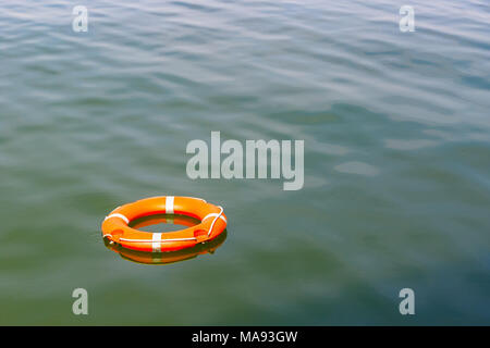 A lifebuoy floating on water for concept use - Stock Photo