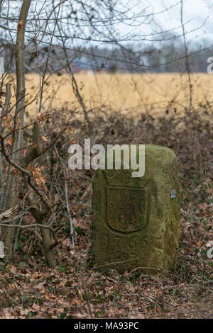 Historical boundary stone on the land border of Netherlands and Germany near the in Dutch called komiezenpaden paths in the past used by border guards - Stock Photo