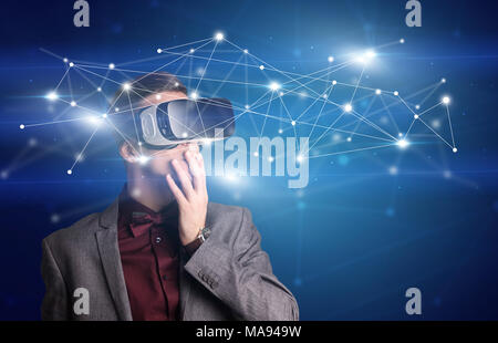 Amazed businessman with virtual reality network concept in front of him - Stock Photo