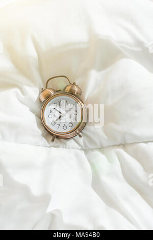 Alarm Clock Showing Eight O'Clock Lying on White Bed Blanket in Bedroom. Bright Morning Sunlight Streaming Through Window. New Day Beginning Waking Up - Stock Photo
