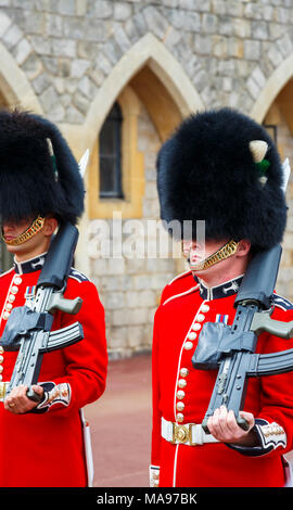 Soldiers in Queen's Guard at Windsor Castle, England, with red uniform and traditional black bearskin cap or busby marching with shouldered arms - Stock Photo