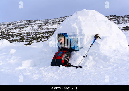 traveler pours himself a hot drink from a thermos, sitting in a snowy house igloo against a background of a winter mountain landscape - Stock Photo