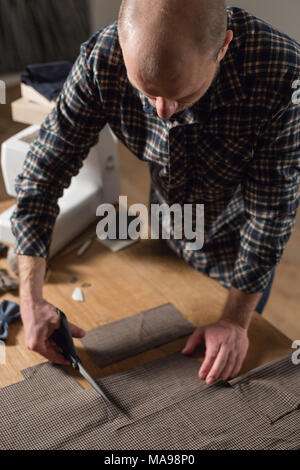 Closeup cutting brown plaid wool fabric. the line pattern. Young man working as a tailor and using a sewing machine in workshop. - Stock Photo