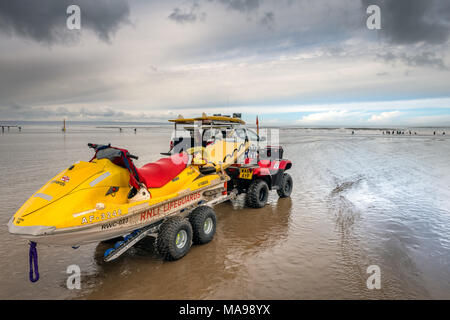 An RNLI Beach Patrol vehicle keeps watch on the surfers at Saunton Sands in North Devon on an overcast Easter Good Friday in the South West of England - Stock Photo