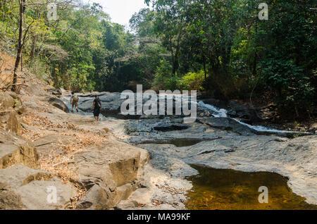 Two boys make their way over rocks on the trek to Mainapi Waterfall in Netravali Wildlife Sanctuary, Goa. - Stock Photo