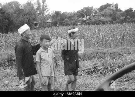 Black and white photograph showing three Vietnamese males, one boy wearing shorts, and two older men wearing long sleeve shirts, one wearing a hat and the other a bandana, standing in front of a field, with trees and houses in the background, photographed in Vietnam during the Vietnam War (1955-1975), 1968. () - Stock Photo
